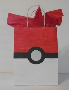 This is the gift bag I made, Danielle. I bought white gift bags and painted the top half red. I used a thick black Sharpie for the line and cut circles for the middle and glued them on. They came out ADORABLE and were a big hit! I got a personalized sticker for the other side from Etsy (not Pokemon....just red and black).