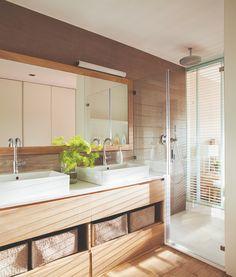 Baño con mueble bajolavabo de madera y cabina de ducha acristalada que comunica con el dormitorio