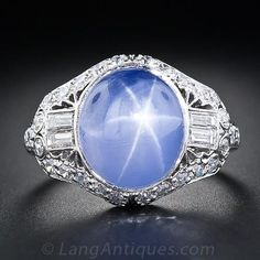 An enchanting velvety lavender-blue star sapphire, weighing 10 carats, and displaying a vivid six-pointed star, is majestically presented in a gorgeous, top notch platinum and diamond setting. This sublime and all original Art Deco jewel, circa 1925, is consummately ornamented with two pairs of shimmering straight baguette diamonds, small sparkling single-cut diamonds, decorative open work and a touch of hand engraving which combine for an artful blending of classic Art Deco geometry and…