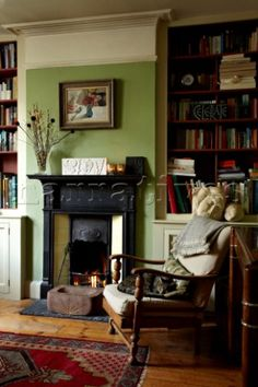 Brighton, UK - cozy fireside space with antiques and books; green walls, ivory trim, wood floors, black fireplace