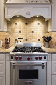 Light travertine mosaic tile blends nicely with the creamy cabinets and warm tones of the granite counter. The metal accent tiles echo the floral motif of the hood ornament, bring out the gray flecks in the counter, and speak to the stainless steel stove.