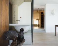 Residential interior: a refurbishment in Clerkenwell. A minimalist bathroom with cast concrete bath, smart glass sliding walls and warm American walnut office snug. Architect: Klassnik.com