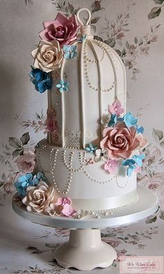 Two- tier birdcage wedding cake has pink, cream and teal blue floral accents....