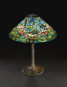 """TIFFANY STUDIOS A FINE AND RARE """"POND LILY"""" TABLE LAMP with a rare """"Water Lily Twisted Stem"""" base shade impressed TIFFANY STUDIOS NEW YORK 1490-5 base impressed TIFFANY STUDIOS/NEW YORK/443 leaded glass and patinated bronze 26 7/8 in. (68.3 cm) high 20 1/2 in. (52.1 cm) diameter of shade circa 1905"""