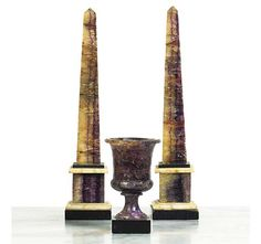 A PAIR OF GEORGE III BLUE JOHN OBELISKS  CIRCA 1800  Of typical form, the stepped plinths intersected with slate and alabaster galleries, restorations  13¼in. (33.5cm.) high;  and a George III Blue John urn, of campana form -- 5½in. (14cm.) high (3)