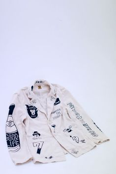 White jacket embroidered / painted with indigo illustrations. Provenance unknown.
