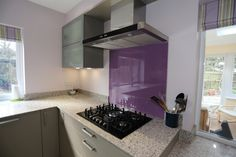 Contemporary/modern shiny grey kitchen with purple splashback and lime accents