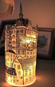 A paper lantern with a view of a beautiful city. Draw it on a piece of stiff white paper or, in this case, wallpaper. Use battery powered lights on a string and put it in a glass jar, put the drawing around the jar and glue it together on the back using a glue gun.
