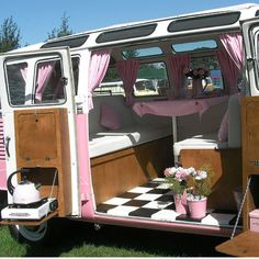 Beautifully renovated camper van . . . the black and white check flooring, white overall background and seating with pink accessories is very cool.