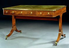 A very fine quality early 19th century ormolu mounted and boxwood inlaid rosewood writing table, the rectangular gilt tooled green leather lined top with a brass banded moulded edge above three short drawers with leopard mask ring handles and three conforming short drawers to the reverse, the splayed legs joined by a high stretcher terminating in brass castors