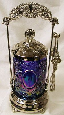 New reproduction of a vintage pickle caster with blue/purple peacock carnival glass insert. 65.00