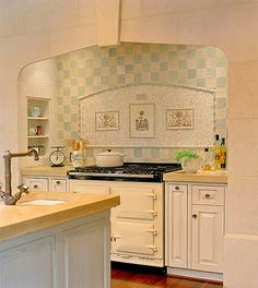 Artfully Arranged Tile Backsplash ~ This subtle checkered pattern on the range backsplash surrounds a mosaic centerpiece that displays three pieces of artwork. The larger squares that frame the piece pair nicely with the tiny squares of the mosaic. The light color scheme blends beautifully with the walls while adding a splash of uniqueness. ~ Love the stove!