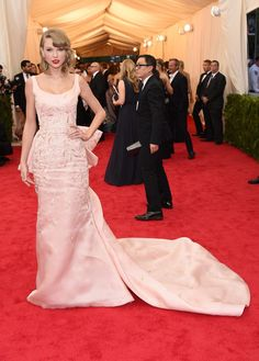 """Taylor Swift looked like the sweetest princess in this embellished pink Oscar de la Renta gown featuring a cascading train during the Met Gala. Swift attended the """"Charles James: Beyond Fashion"""" Costume Institute Gala at the Metropolitan Museum of Art on May 5, 2014 in New York City."""