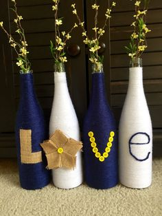 These wrapped wine bottles make the perfect decoration for your home! Each bottle is wrapped in white and navy blue yarn. Burlap, yellow buttons, and