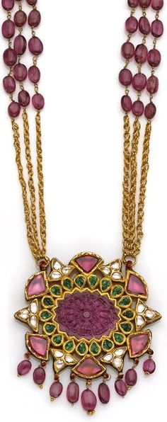 A Moghul style ruby, emerald, diamond and gold pendant necklace the openwork oval pendant centering a carved ruby of floral design within a frame of leaf-shaped emeralds and further surround of table-cut rubies and diamonds with edges of red enamel, suspending a ruby bead fringe, the reverse of similar design, completed by a three-strand fancy-link chain with ruby bead detail; length: 23½in.