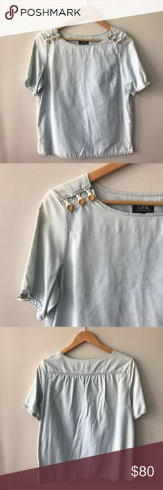 """A.P.C. Chambray Top Breezy short sleeve authentic A.P.C. chambray top with great details.  ·  Elastic sleeve hem with rope detail ·  Wooden buttons near neckline ·  Laying flat approx. 20"""" across underarm to underarm & 25.5"""" long ·  100% cotton – feels like linen, has some texture (not pilling) ·  Machine Wash  Lightly worn & washed a few times. Some areas are lighter than others – not a flaw – a design of the fabric. No stains, holes, or pilling. In great, pre-owned condition. Bundle & save…"""