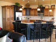 alder cabinets, beautiful black kitchen island with bar seating