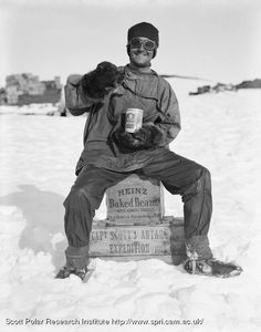 Expedition member sits on two boxes marked 'Heinz Baked Beans', on the snow.