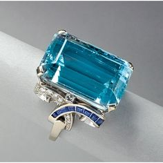 for AQUAMARINE, SAPPHIRE AND DIAMOND RING, ca. 1950. Erwin Reu Co., Newark. Rectangular step cut aquamarine, 22 cts. by formula, Volute shoulders, set with graduated circular cut diamonds and calibre cut sapphires, 14k wg. 8.1 dwt. (12.6 gs.