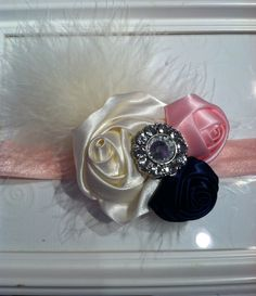 Ivory satin rosette flower with mini light pink and royal blue satin rosette flowers with jewel center and marabou attached to a light pink elastic headband