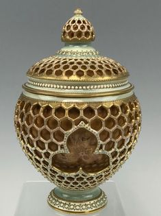 """Zsolnay fully reticulated jar or covered urn with a very interesting honeycomb outer layer and an iridescent copper inner layer with gold detailing. It's a highly textured, lovely piece from Zsolnay.  The jar is about 7-3/4"""" tall and about 4-1/2"""" in diameter in the middle E18/E225e"""