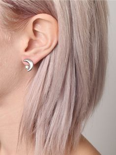 Small, silver tone crescent moon and star earrings featuring a matte finish with post backs