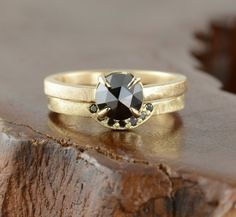 Natural black diamond rings in 14k yellow gold.   The engagement ring features a top quality black rose cut diamond. The diamond is jet black