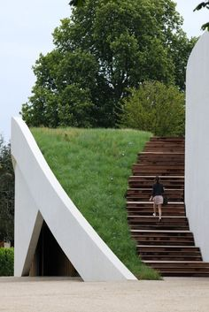 White wall forms balustrade along edge of grass before drop to basement