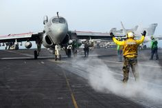 A Sailor directs an EA-6B at sea. by Official U.S. Navy Imagery