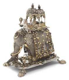 An Indian silver and parcel-gilt filigree elephant, third quarter 19th century the filigree elephant mounted with double-domed howdah enclosing a rajah, flanked by lanterns, with mahout before; the canopy applied with flowering plants repeated on shaped rectangular base, raised on four massive paw feet, apparently unmarked height 12 5/8 in.