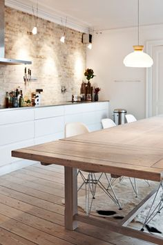 Beautiful, simple kitchen. Clean white lines and a fantastic brick wall.