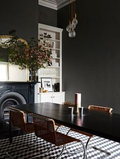 A dark and moody dining space with dried flowers and a modern light fixture