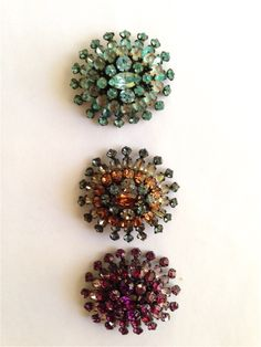 Trio of brooches in different colors