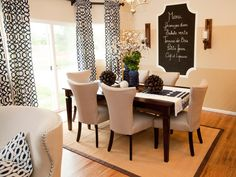 In this open plan neutral dining room, a whimsical chalkboard on the wall provides the perfect spot for writing up the menu. Boldly patterned black and white curtains add visual interest without taking over the space.
