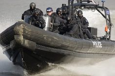 Armed Metropolitan Thames River Police Boarding Teams, on an Olympics maritime security exercise in conjunction with the Royal Marines, London. Practicing boarding techniques in a Rigid Inflatable Boat (RIB).