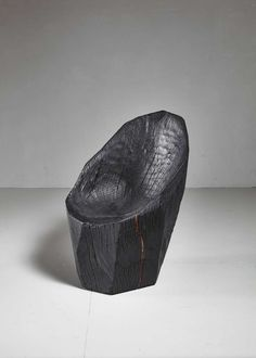 An 'Ausgebrannt' chair made from a solid piece of oak from a naturally fallen tree by Belgian artist Kaspar Hamacher. Hamacher (1981), son of a forester, uses nature as the main inspiration for his work, with wood being his preferred material. This piece was bought directly from the artist himself.