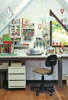 """Na área ampla sob o telhado, Fabiana cria suas kokeshis, bonecas de madeira à moda japonesa. """"Preciso de tudo à mão!"""" A arrumação impera. Os rolos de fita enfileiram-se em um suporte de papel-toalha, enquanto as tesouras ficam em uma placa de madeira encapada de tecido. Como as kokeshis são cheias de detalhes, o pendente sobe e desce conforme a necessidade de iluminação na bancada de trabalho.Fotos Alessandra Okazaki (SC)"""
