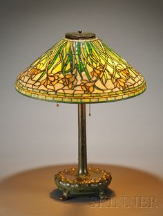 Tiffany Studios Daffodil Table Lamp   Patinated bronze and mosaic glass   New York   Conical shade in the daffodil pattern over three sockets raised on circular base with relief decoration supported by four paw feet, shade marked Tiffany Studios, New York inverted, no. 1497-25, some heat checks in glass normal for its age, base marked Tiffany Studios New York, no. 359, ht. 25 1/4, shade dia. 20 in.
