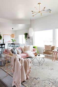 This room is so collected and cozy! Love the pink couch, brass light and dowel chairs!