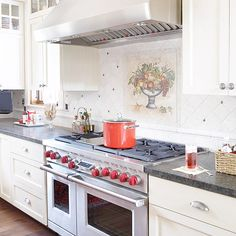 tumbled marble tile backsplash with pewter accents, create a warm and traditional kitchen. Most of the tiles are installed at a diagonal, but a rope border tile sets off a row of vertical tiles along the countertop, forming a design that plays with pattern without becoming too flashy.