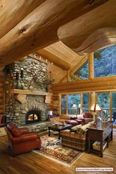 What a stunning yet cozy cabin great room~~~ Exquisite beam work with a river rock fireplace!
