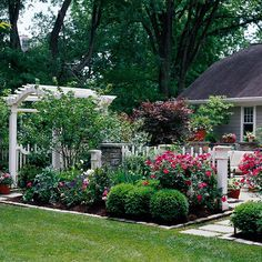 White Fencing - In this small backyard, scalloped radius fencing defines each outdoor room.