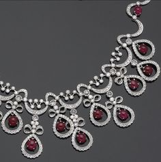 A diamond, ruby and eighteen karat white gold necklace  the necklace designed of scallop-shaped links set with round brilliant-cu diamonds, accented by round and oval-shaped ruby cabochons, suspending diamond-set fringe pendants of bow motif tops and drop-shaped frames, centering oval-shaped ruby cabochons; estimated total diamond weight: 12.50 carats; length: 15in.