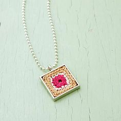 This granny square is anything but antiquated. Crocheted with three colors of embroidery floss, it achieves eye-catching distinction in diminutive size, making it perfect for showing off on a pendant.