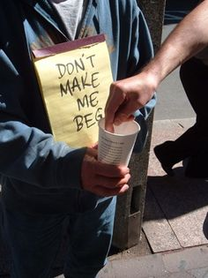 """This picture is ironic since the sign says, """"Don't make me beg,"""" yet the person is """"begging"""" for money.  This helps this person to get money because the use of a literary device catches the attention of people passing by."""