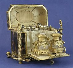<b>A 19th century French Palais Royale ormolu mounted tortoiseshell combined scent/sewing casket,</b></i></u> with floral enamelled set lid and fall front revealing fitted interior containing two enamel and ormolu mounted glass scent bottles and eleven (ex 12) sewing implements, <i>8ins</b></i></u>