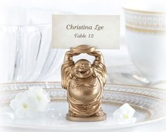 """Eastern-inspired, with wishes desired! Our """"Happy Buddha"""" Place Card/Photo Holder wedding favor symbolizes happiness, contentment and prosperity--everything you'd hope for in life, not just for yourself, but your guests as well! Features and facts:    Finely detailed gold, smiling Buddha with arms holding up slotted tray for place card or photo  Buddha is crafted from heavyweight resin  Matching antique-gold place card included  #weddingfavors"""