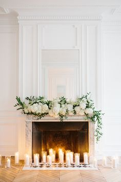 Tall candles in glasses and greenery plus lush white hydrangeas make the fireplace look very elegant and very chic. in fireplace wedding Fireplace Wedding Décor With Tall Candles In Glasses And Greenery