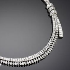 A diamond necklace, by Boucheron, circa 1955 Designed as two graduating rows of marquise, baguette and step-cut diamonds, each side accented by three ribbons of baguette-cut stones, issuing a partial third row of graduated baguette-cut diamonds to the front, diamonds approximately 26.60 carats total, signed Boucheron Paris, maker's mark, French assay marks, length 38.0cm.