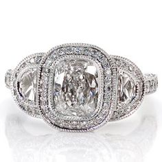 This dazzling diamond engagement ring is vintage inspired and will sparkle like a start. The band is done in micro pave & filigree, and the top of this stunning ring is a three stone, bezel set halo design shown here with a 1.00ct Cushion cut center diamond and two half moon diamonds. Design 1815 from Knox Jewelers